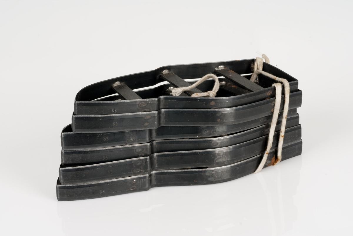 Stansekniver av stål. 6 stansekniver bundet sammen med skolisse. Stanseknivene brukes til modeller for forskjellige skostørrelser. De forskjellige størrelsene er 34, 35, 36, 37, 38 og 39, og er inngravert. Men på hver stansekniv er det en påklistret teipbit med annen størrelse skrevet på. Disse størrelsene er 33, 34, 35, 36, 37 og 38.