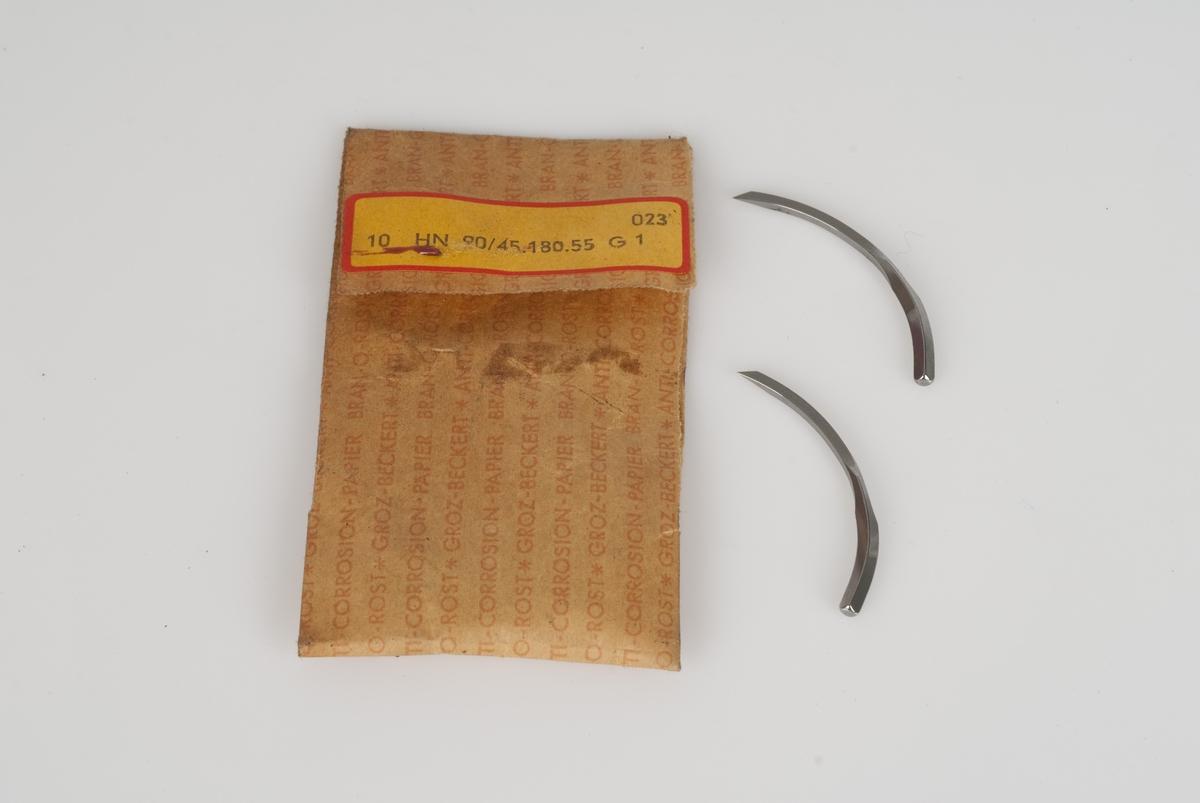 Nåler av metall i papirpose. Gul merkelapp med påført tekst på posen.