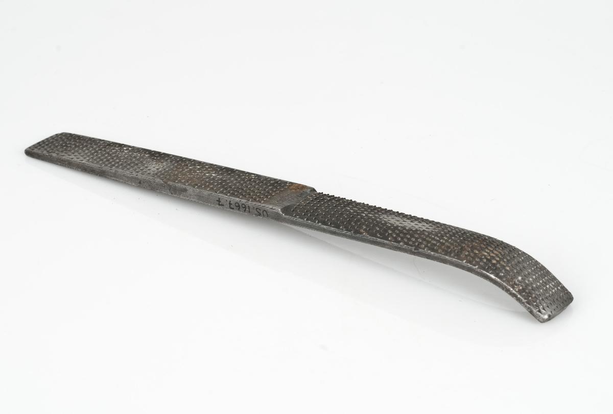 Såleasp av metall med raspegrad og dobbeltgrad/krysshugget grad. Den ene enden av raspen er bøyd.