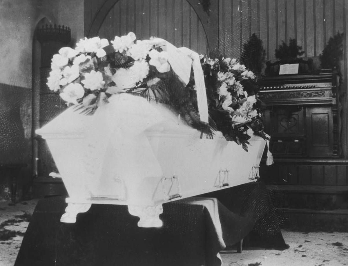 Ole Berge's begravelse. Kirste dekorert med blomster.