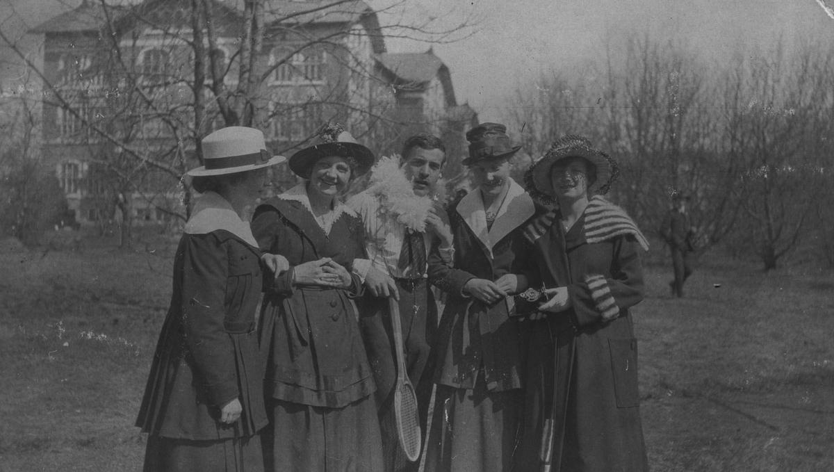 5 personer, 4 kvinner og 1 mann for urbygningen, baksiden