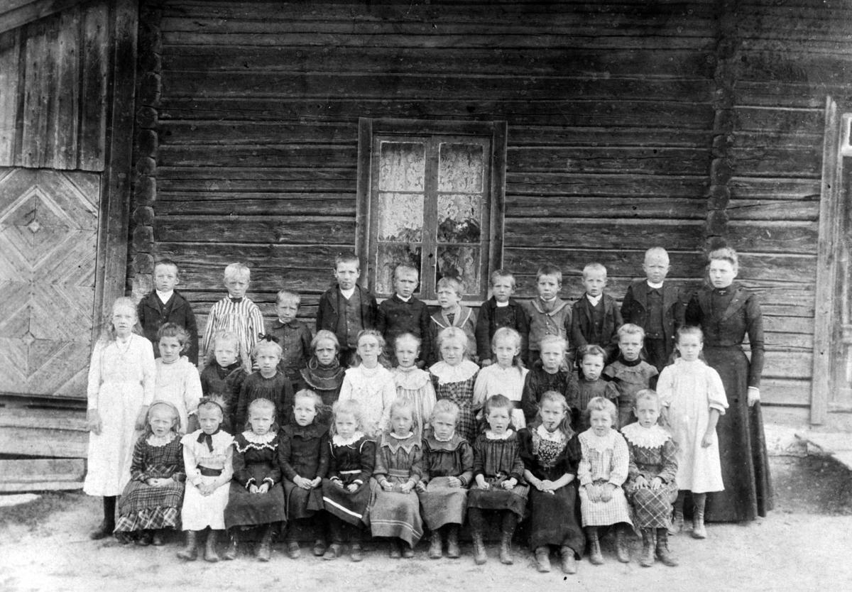 Elever og lærerinne på Aamodt skole ved Nygard.