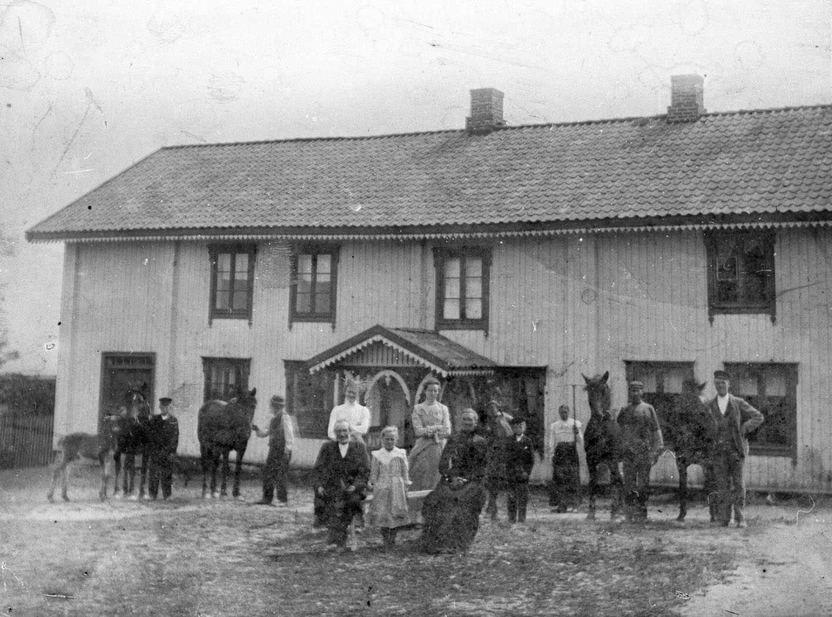 Nitteberg. Familen, tjenestefolk og hester samlet på tunet foran hovedhuset. Trolig i slåtten, ei jente i bakgrunnen står med ei rive.