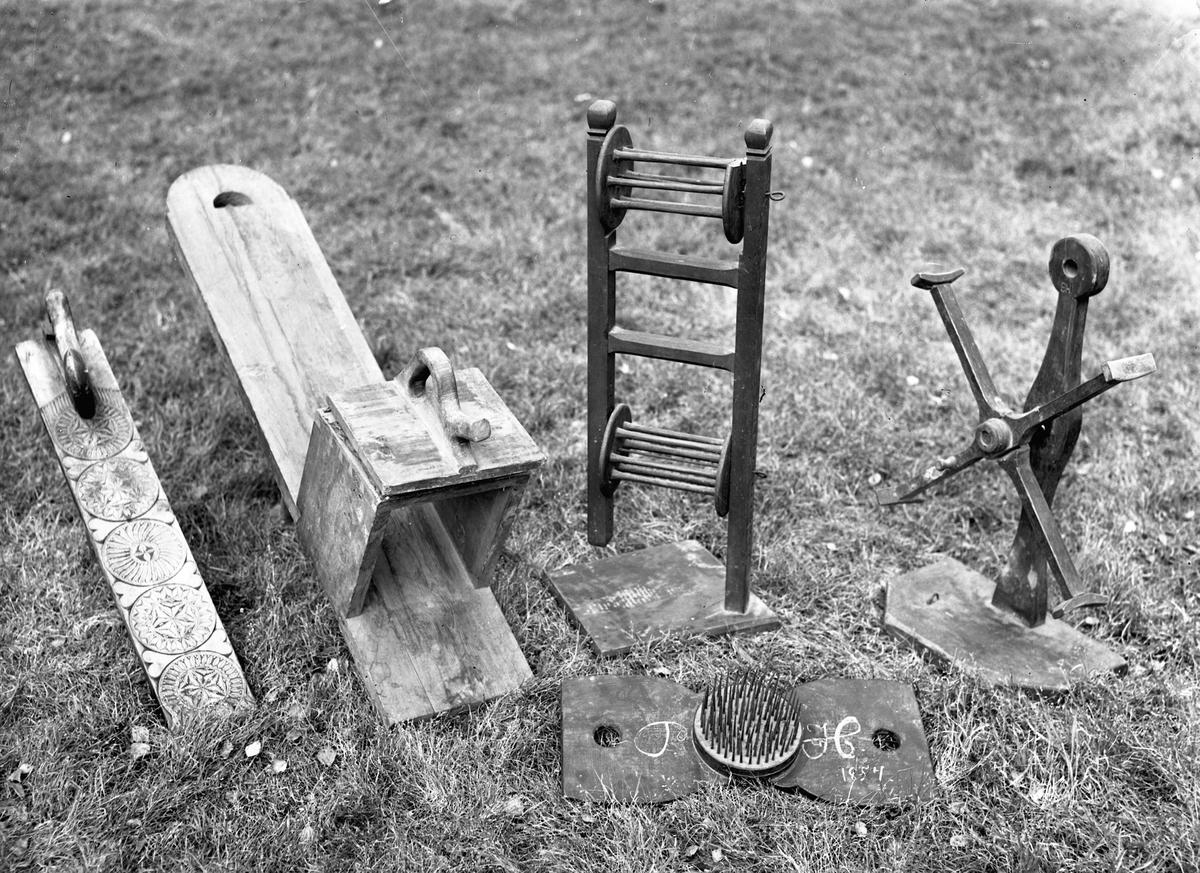 """Redskaper til behandling av garn. Fra v.: strykebrett, strykebrett, garntvinne, kam/karde til lin merket """"PH 1854"""", garntvinne."""