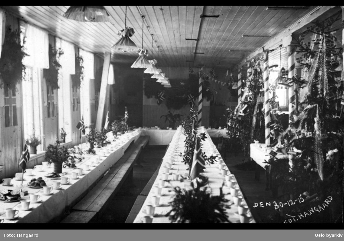 Postkortfotografi av bord dekket med krus og fat med julekake og boller. Bordet er pyntet med norske flagg og gran. Juletrær langs den ene veggen og norske flagg på den andre. Sannsynlig fra Høie fabrikker