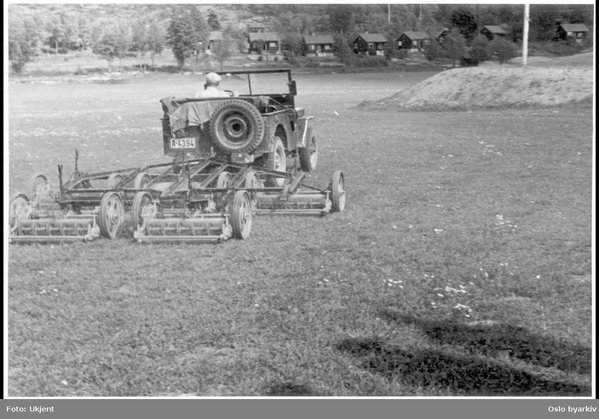 Jeep trekker gressklipper-maskin på sletta. Sanitetsforeningens hytter for tuberkuløse i bakgrunnen.