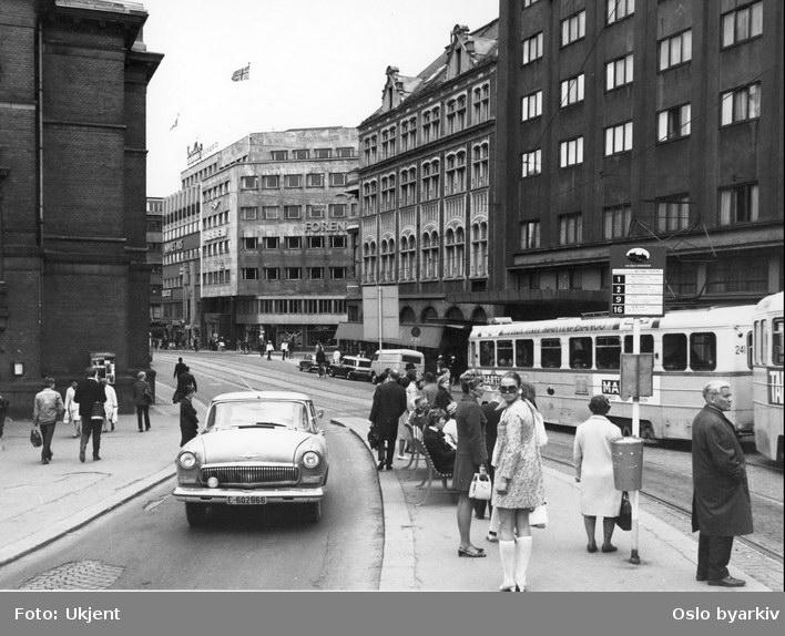 Oslo Sporveier. Trikk motorvogn 241 type Høka MBO linje 2. Bil av merket GAZ Volga, oppsatt prøve på nytt stoppestedskilt. Gatemiljø i Stortingsgata ved Hotel Continental.