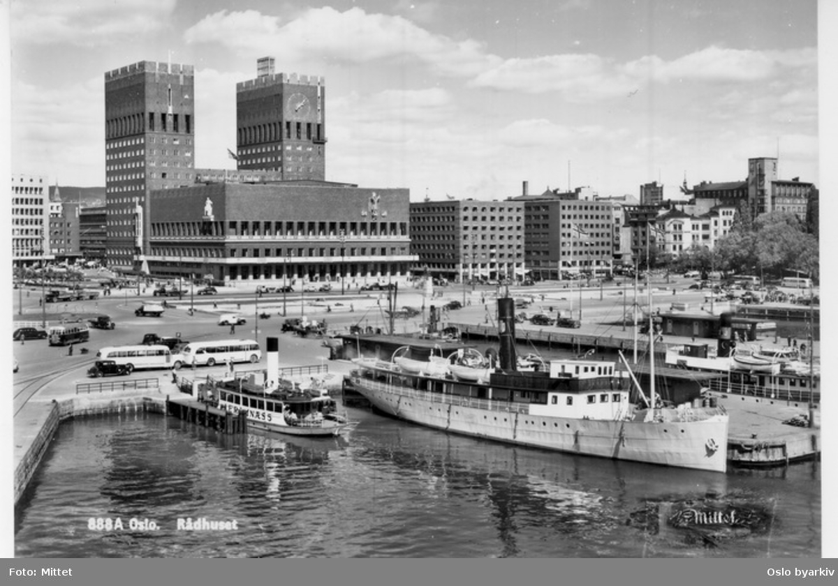Rådhusbryggene (utstikkere) med dampbåter. Rutebåten D/S JARLSBERG som ligger ved utstikker D tilhørte Tønsberg Dampskibsselskap A/S (P. Johannessen Rederi), som gikk i rute mellom Tønsberg og Oslo inntil ca. 1956. Rådhusplassen, Oslo Rådhus. Busser, biler. Postkort 888A.Datering: 1950-53