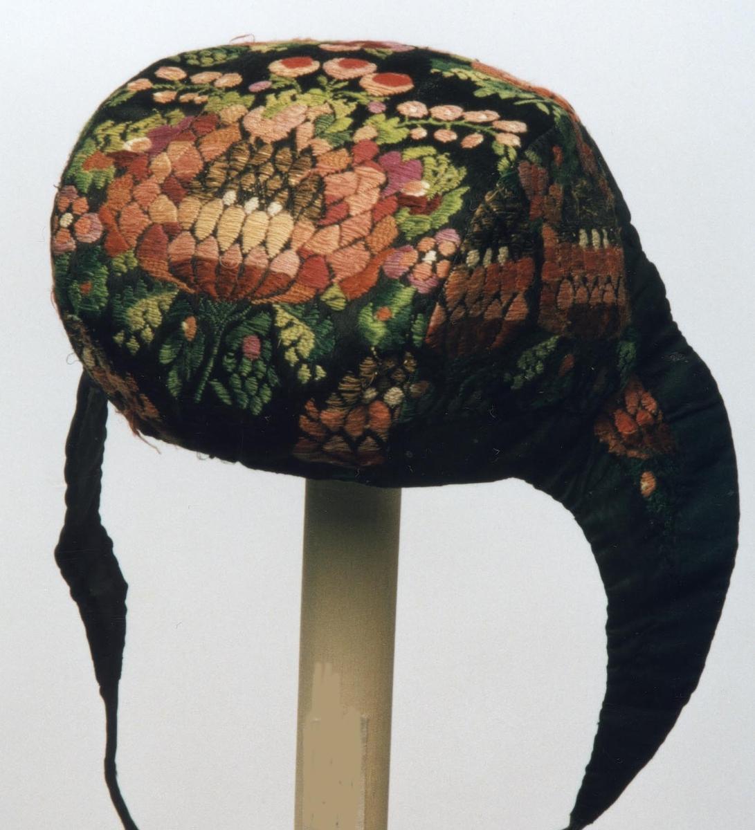 Vevet og utbrodert mønster i frodige farger. 2 knyttebånd. Opplysninger gitt av faglærer ved Kunsthåndverksskolen på Røros, Eva Wahl Sandnes, november-1977.