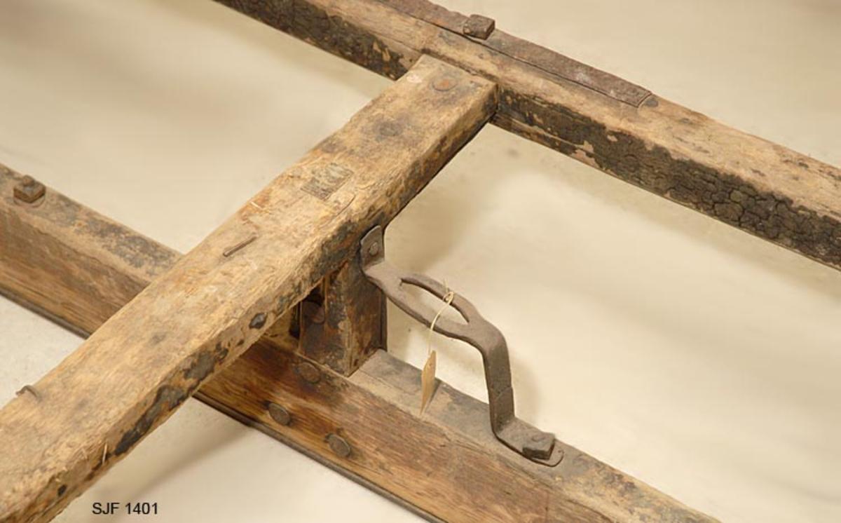 Tømmerslede m/6 stokker. Sledens meier har jernskoning i hele meiens bredde. Skoningen er foran bøyd rundt meienes ender og ca. 1/2 m bakover på meiens overside.  Sleden har 4 tverrgående fjetrer som er 92 cm brede og står i en avstand av ca. 70 cm. Fjetrene hviler på 12 cm høye fjetrestamper som er forsterket med jernbeslag. Sleden er forsynt med 5,5 cm brede veimeier som stikker ca. 20 cm ut fra meiene.  Fjetrene er innfelt i veimeiene, og sammenføyningene er forsterket med jernbeslag på veimeiens overside. Veimeiene har jernbeslag foran på krumningenes ytterside. Foran på sleden er det felt inn et tverrgående hutre i meiene. Dette har to hull (5 x 6 cm)til å feste lenkeforbindelsen til skjekene. Hullene er forsterket med jernbeslag. Bak det nest bakerste fjetret er det et jernbeslag til å feste øksa i. Materialet i sleden er bjørk. Den bærer rester etter tjærebredning. På sleden ligger 6 barkede furustokker. Stokkenes lengde er: 13 hm, 12 hm, 11 hm, 8 hm, og to på 10 hm. På sleden følger det med en bendstang (2, 10 m) og en bendkavle (0, 8 m) til å stramme kjettingen med. Sleden er laget på Nyborg. Den er brukt til framkjøring av tømmer.   Jfr. forbindelse med stuttingen SJF.01402.