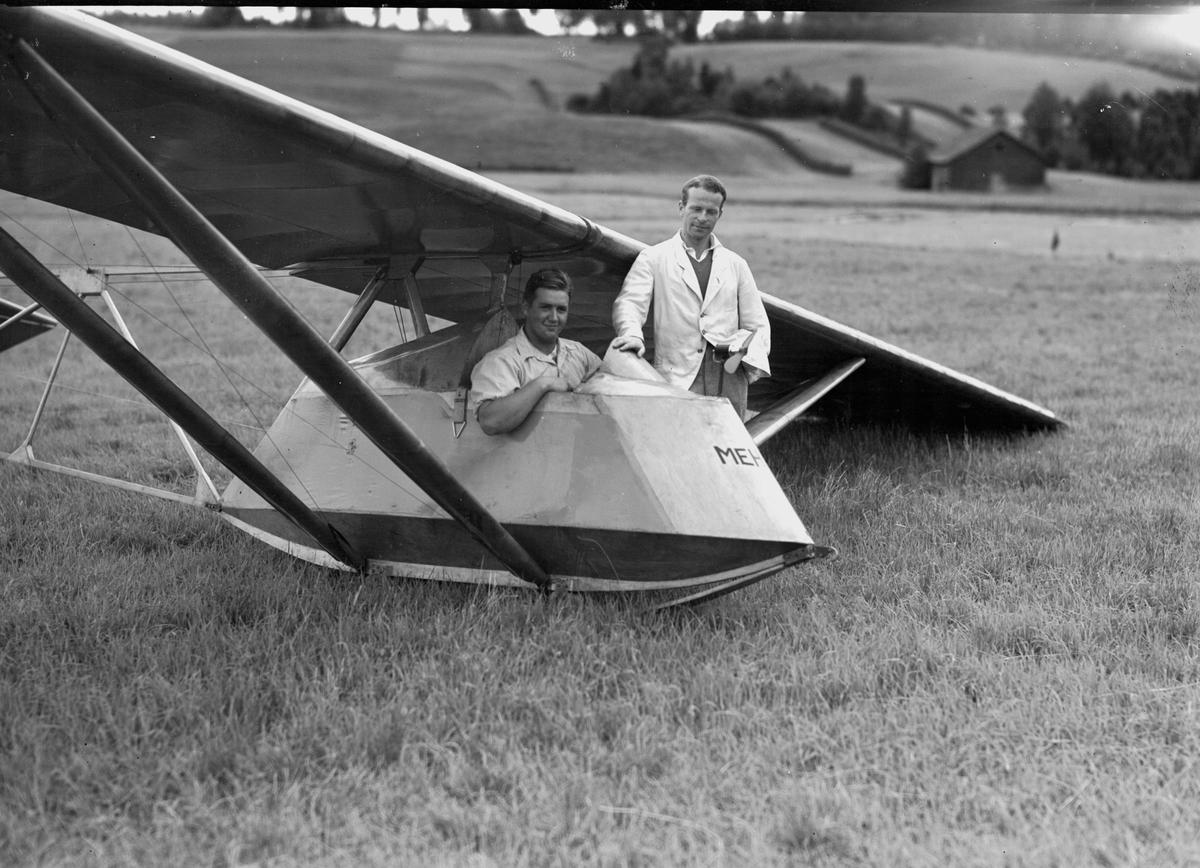 To ukjente menn med seilfly i enga, gård i bakgrunnen. MEH på flykroppen.  Dette er LN-ABM Mehank. Det fyrste glideflyet bygd av Aal Flyveklubb.