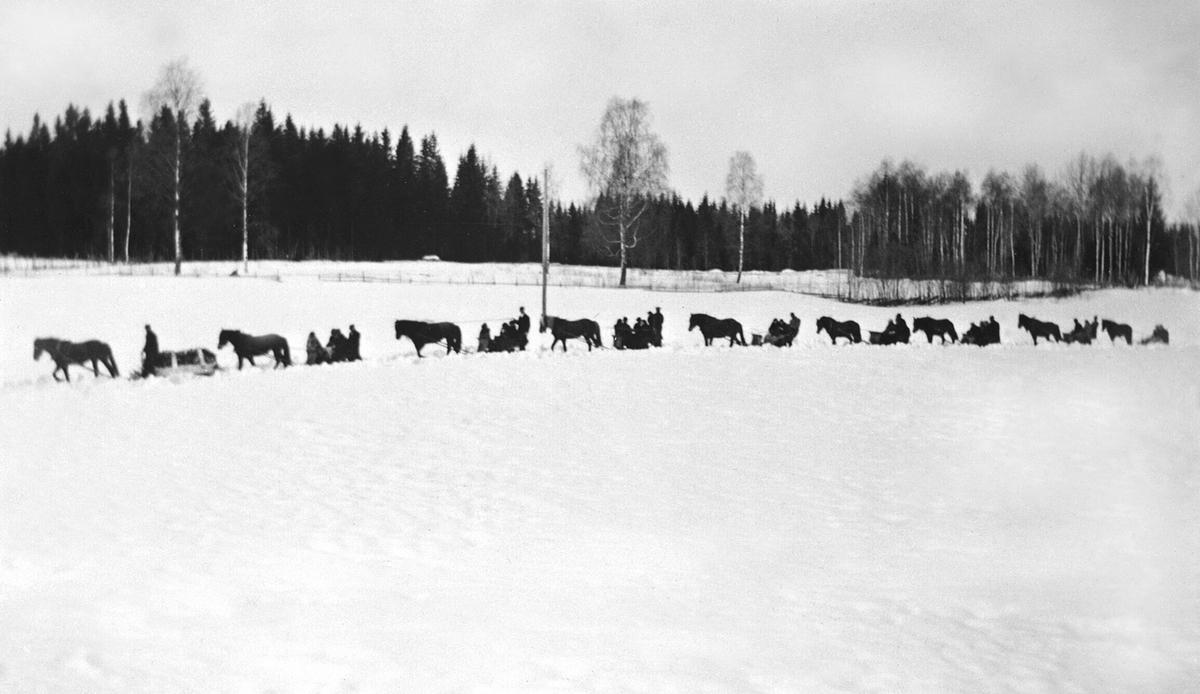 Begravelsesfølge med hester og sleder etter Karoline Brenden den 18. mars 1936. Gravfølget kommer kjørende ned fra Enger mot Purkilstad, Stavsjø, Hedmark.