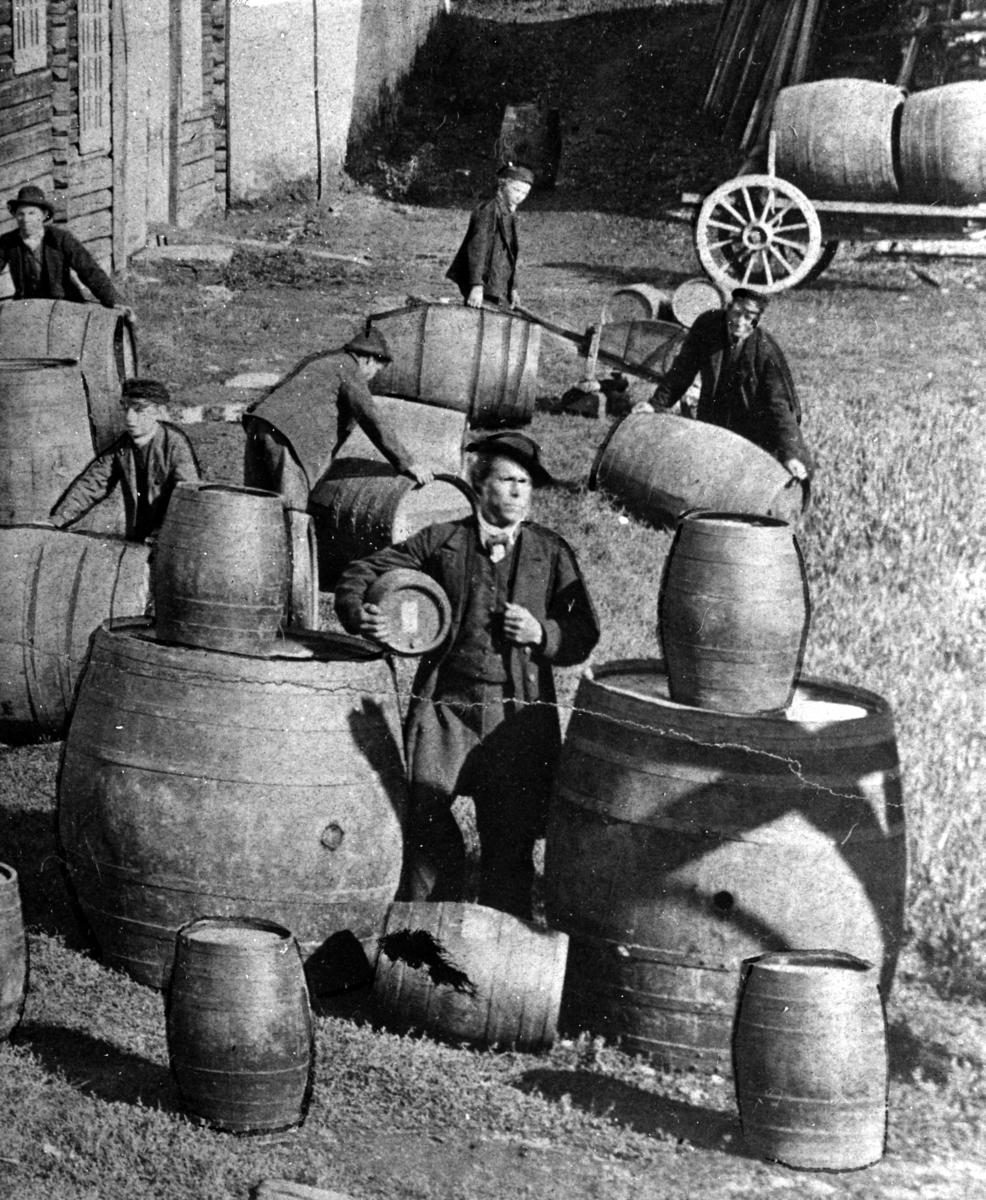 Løiten Brenneri, Løten. Brenneriarbeidere, eiketønner, fat, ukjent mann med 40 potters anker under armen.  Normann repro NR-6335.