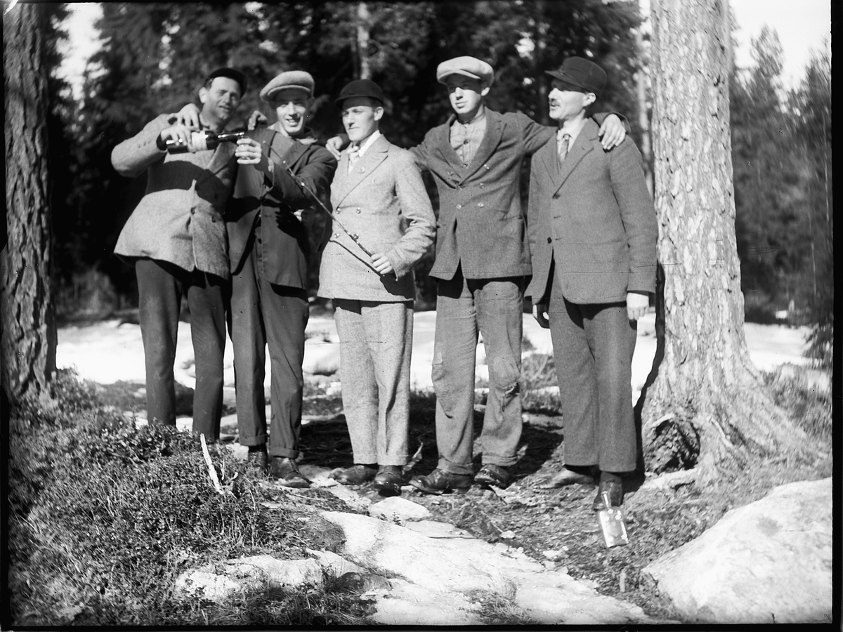 Fem ukjente menn. En holder et glass mens den andre heller fra en flaske.