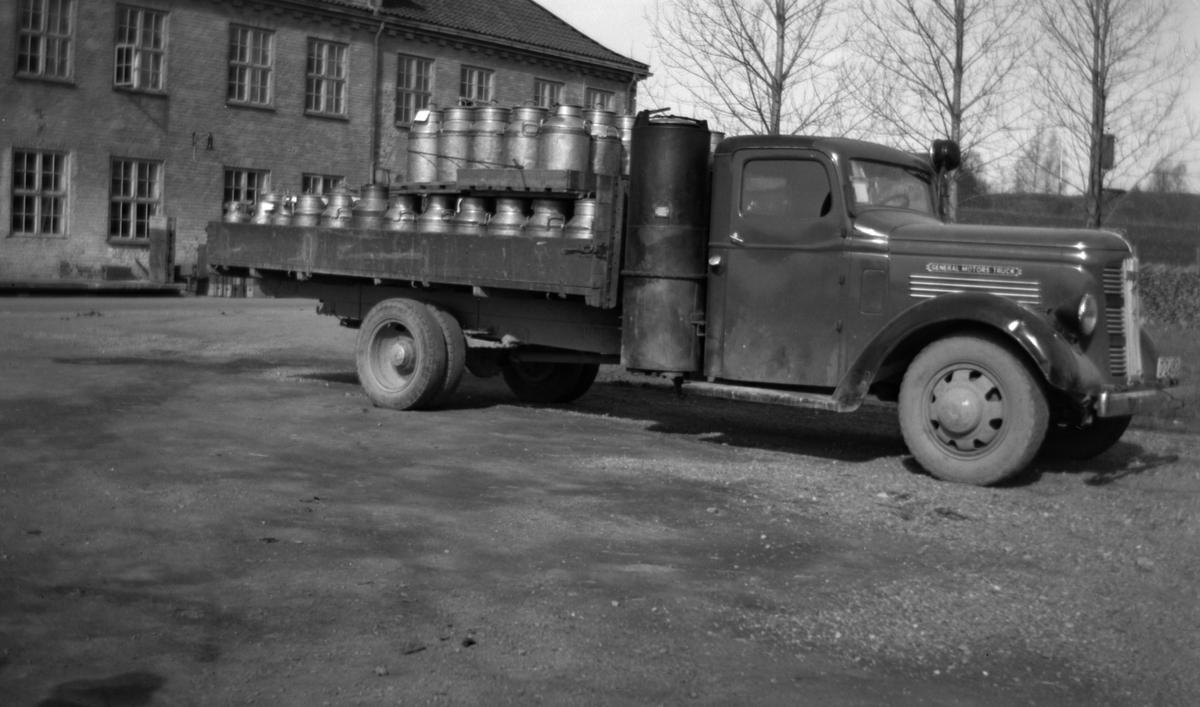 HAMAR JERNSTØPERI OG MEK. VERKSTED, HAM-JERN, LASTEBIL D-2483, GENERAL MOTORS TRUCK, KNOTTFYRING, GENERATOR, MJØLKEBIL UTENFOR HEDMARK MEIERI. GENERAL MOTORS TRUCK (GMC) årsmodell 1937. Knottgeneratoren tilsier at bildet er tatt 1940-45.