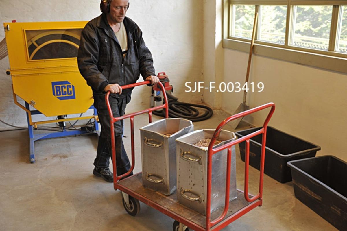 """Frode Murud ved Skogfrøverket på Hamar triller to aluminiumsbeholdere med granfrøhams inn i det rommet i frøverksbygningens andre etasje som var innredet med henblikk på våtavvinging.  De to beholderne var lagd av aluminium og hadde to handtak på den flate """"baksida"""" og en antydning til """"nepp"""" (""""helletut"""") på motsatt side.  Granfrøhamsen besto av uavvinget frø.  Frøvingene, som i naturen bidro til å gi frøet oppdrift, slik at det seilte et stykke bort fra det skyggekastende mortreet før det nådde bakken, var uhensiktsmessig i ha med når frøet skulle brukes i skogplanteskoler eller til direktesåing i skogen.  Vingene kan fjernes på flere måter, men i dette tilfellet dreide det seg om våtavvinging.  Frøhamsen ble helt over i beholderne på tre betongblandere som sto i det rommet der fotografiet er tatt.  Deretter blanderne satt i rotasjon, og det ble sprøytet inn finforstøvet vann.  Den fuktige frøhamsen ble eltet noen minutter.  Deretter ble det tilført blåseluft gjennom slanger fra et par støvsugerliknende maskiner som var montert over betongblanderne, på ei søyle.  Den roterende bevegelsen kombinert med tilførsel av blåseluft fikk massen til å tørke, og frøvingene til å virvle opp og ut av betongblanderen.  De falt deretter ned i vide kar, som var plassert foran betongblanderne.  Frøet ble liggende igjen i beholderne.  Det ble seinere renset på en maskin i et tilstøtende rom.  Da dette fotografiet ble tatt hadde Skogfrøverket også fått en spesialmaskin for frøavvinging.  Vi skimter maskinen, som er gul, inne ved veggen til venstre i bakgrunnen.  Ved denne anledningen var den imidlertid full av furukongler, og Frode Murud fant det like greit å bruke betongblanderne.  Fotografieter tatt i frøverksbygningens andre etasje våren 2011.  Frode Murud har ei foret arbeidsjakke på overkroppen, fordi denne delen av bygningen var uisolert og forholdsvis kald.  På hodet hadde han øreklokker som skulle skjerme ham mot den monotone maskinduren, og i stedet gi ham tilgang til radiop"""
