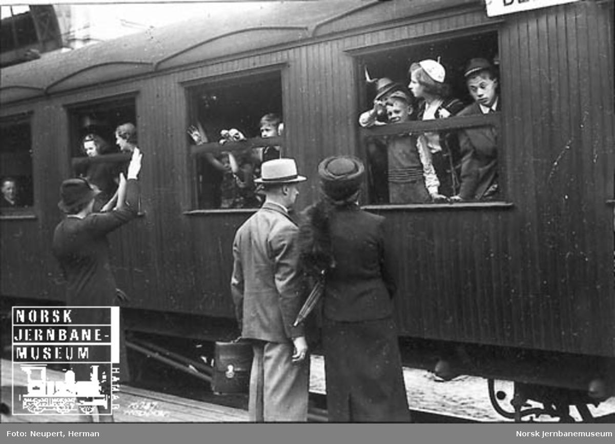 Reisende tar farvel utenfor en vogn på Østbanen