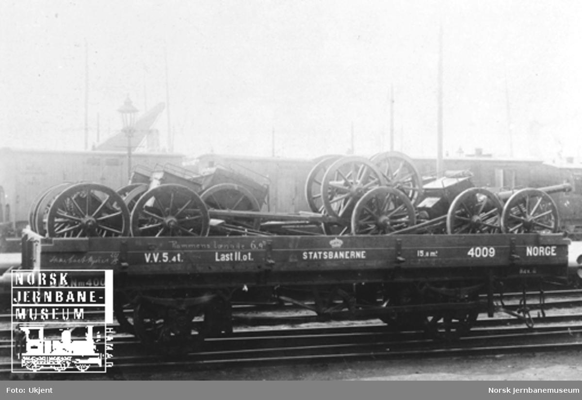 Smaalensbanens vogn litra Nm nr. 4009 lastet med artillerimateriell; fire lavetter med forst., reservehjulskjerre og essekjerre