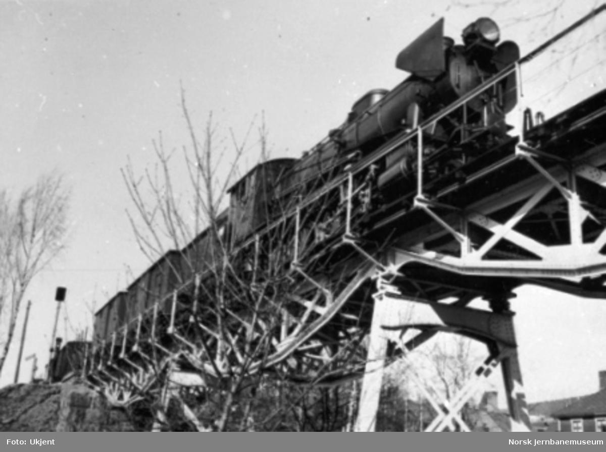 Damplokomotiv type 30a foran godstog på viadukt over Bryggevegen, fotografert på skrått nedenfra