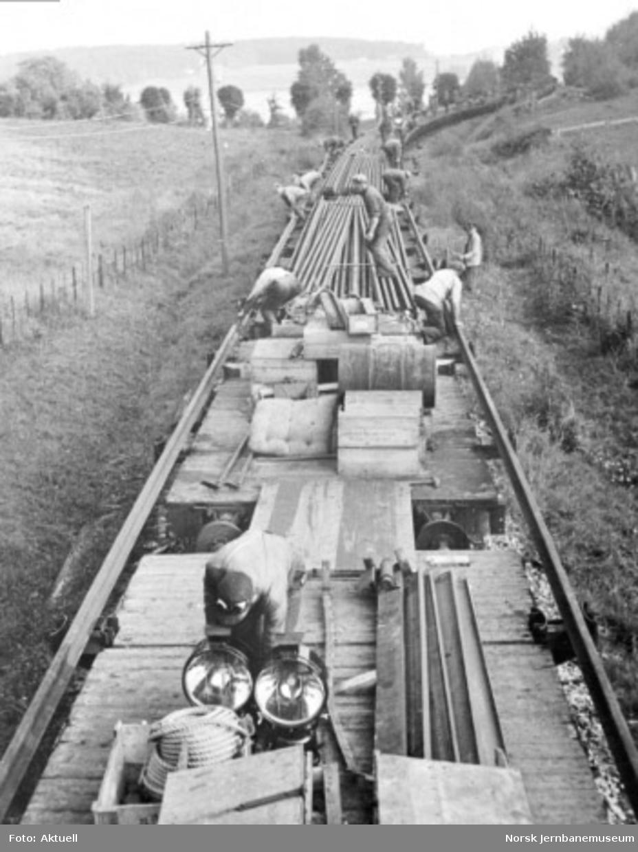 Vestfoldbanens omlegging til normalspor : banemannskap i gang med utkjøring av nye skinner; langt skinnetog