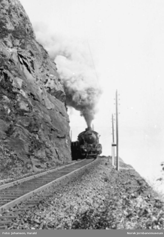 Et damplokomotiv type 29a under full damp på vei opp Ofotbanen med tomt malmtog