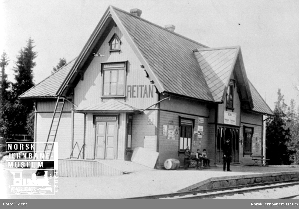 Reitan stasjon med stasjonsmesteren på plattformen og seks unger på benken