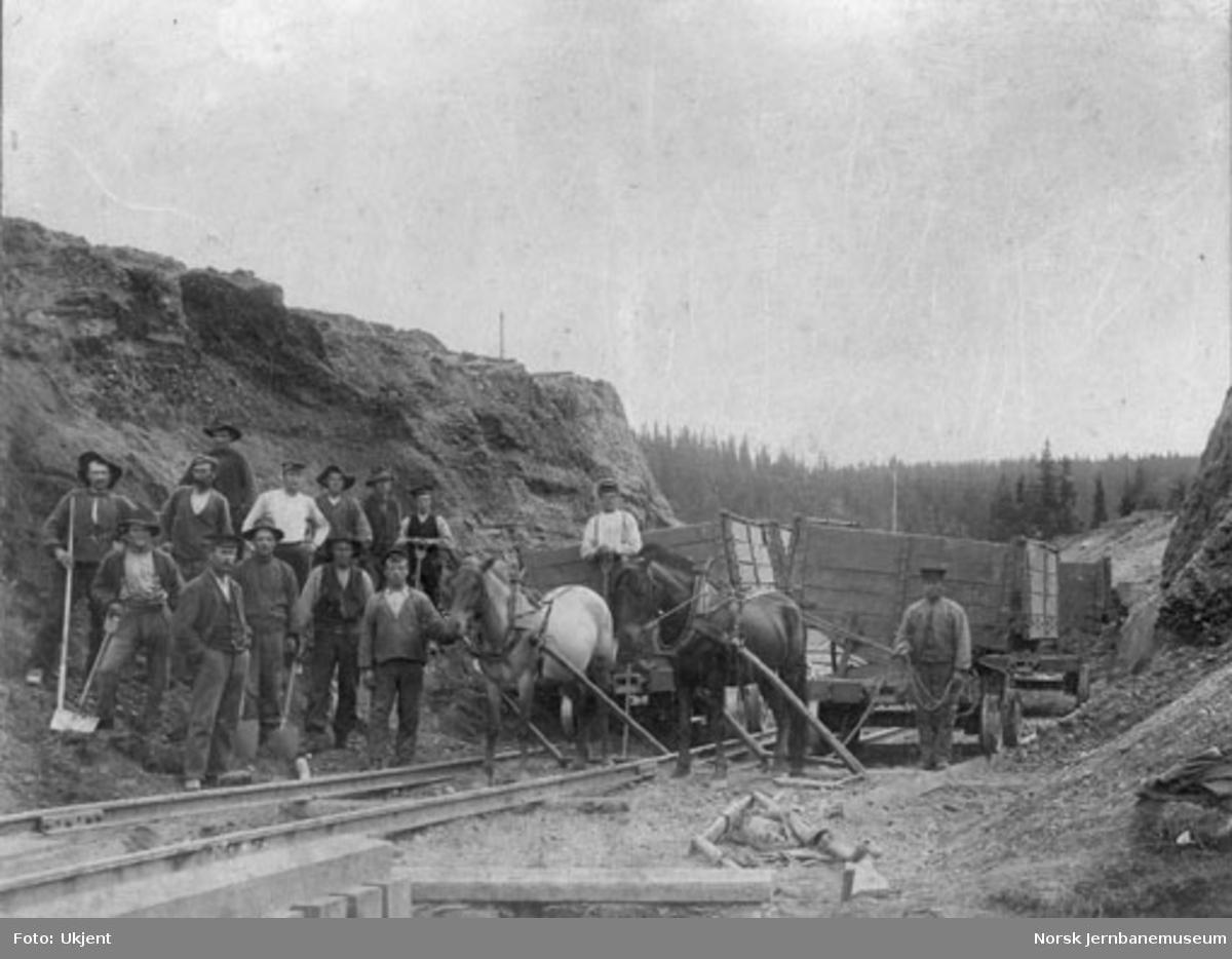 Anleggsarbeide i en skjæring med to hester med vagger og et lag på 14 mann
