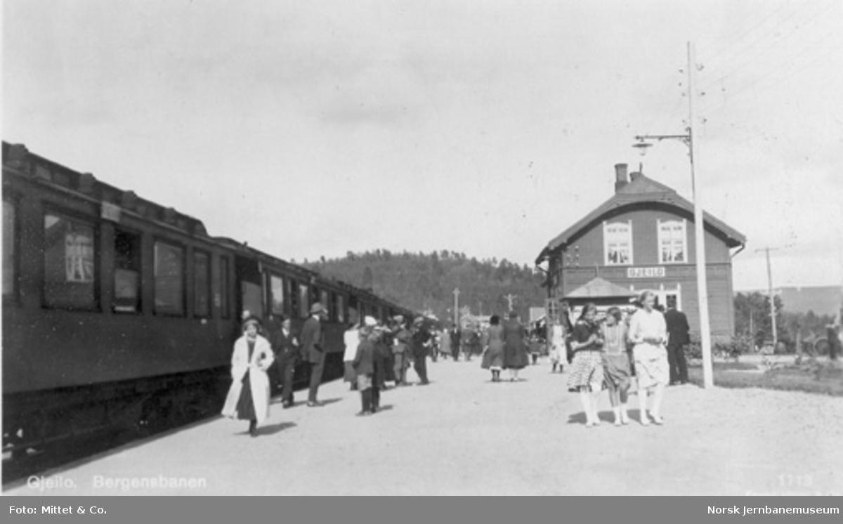 Geilo (Gjeilo) stasjon med reisende og tog i spor 1