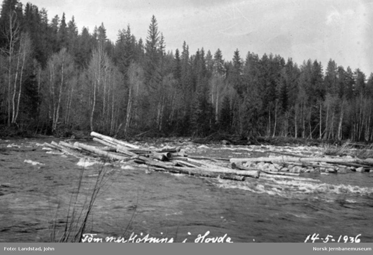 Tømmerfløting i Hovda elv med oppdemmet tømmer på holmen nedenfor vegbrua før hovedmassen ble sluppet