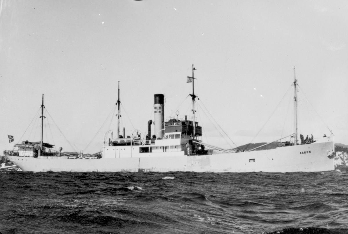 """Dampskipet D/S """"Karen"""" nær land. Deler av mannskapet på baugen. Hus og fjell i bakgrunnen."""