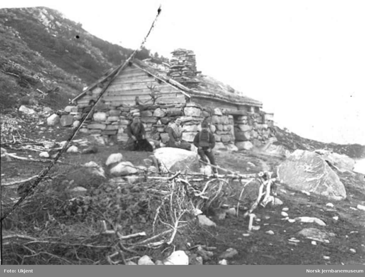 Seterhus med to kvinner og en mann oppstilt for fotografering