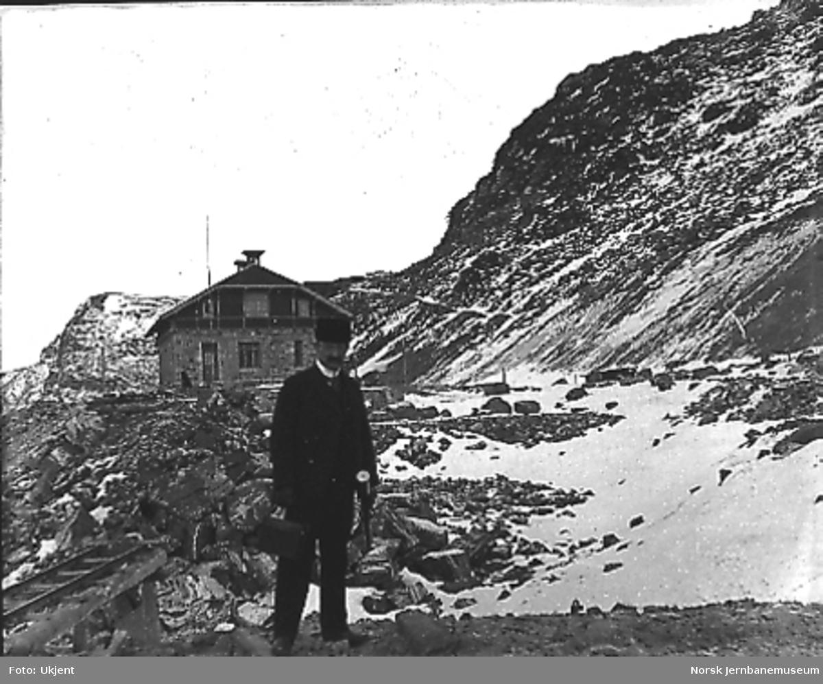 Stasjonsanlegget på Myrdal under arbeid, ferdig stasjonsbygning i bakgrunnen, en mann i forgrunnen