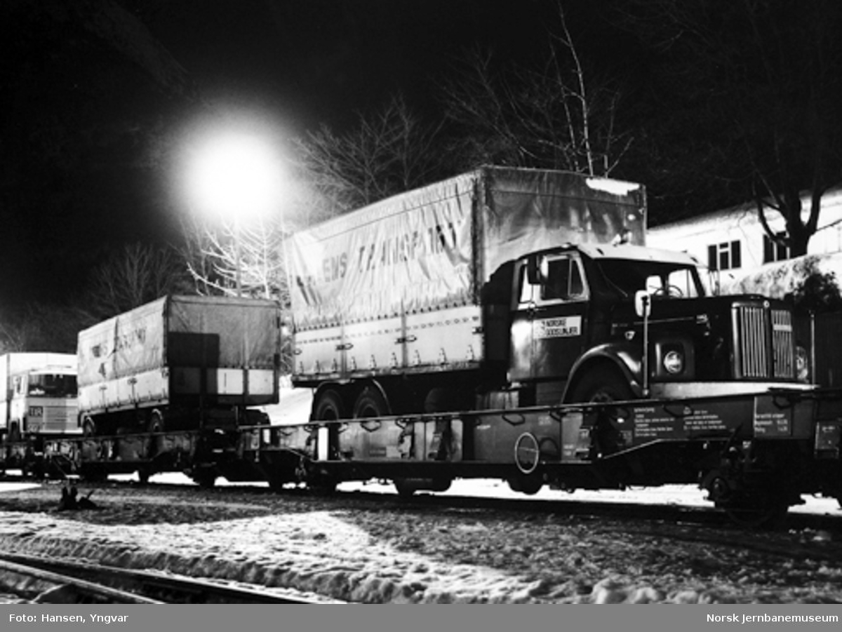Lastebiler og tilhengere opplastet på dyplastevogner på Åndalsnes stasjon