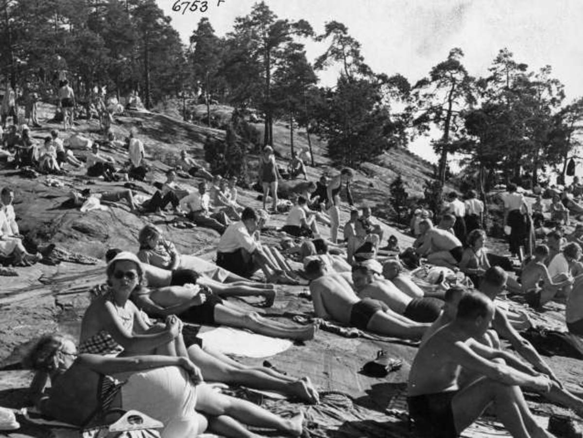 Strandliv med badegjester som soler seg på svaberget ved sjøen på Ingierstrand bad utenfor Oslo.