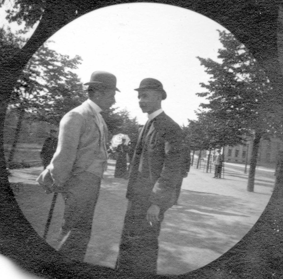 To unge menn står og prater i Studenterlunden, Oslo. Universitetet skimtes mellom trærne. Studenter fra 1892.