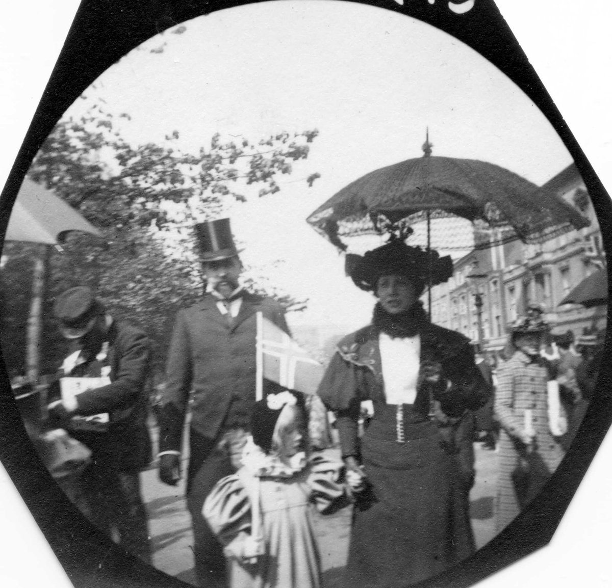 Skuespiller Ludvig Bergh, hans kone Milly (tidligere Thaulow) og datter på Karl Johans gate i Oslo 17. mai,  med norsk flagg, antakelig.Fotografert etter 1906.