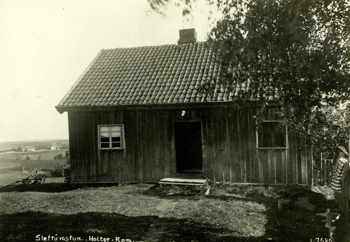 Slættumstuen, Nannestad, Øvre Romerike, Akershus. Lite våningshus sett mot gårdsplassen, hesteredskap ved siden av huset og utsikt mot bygda.