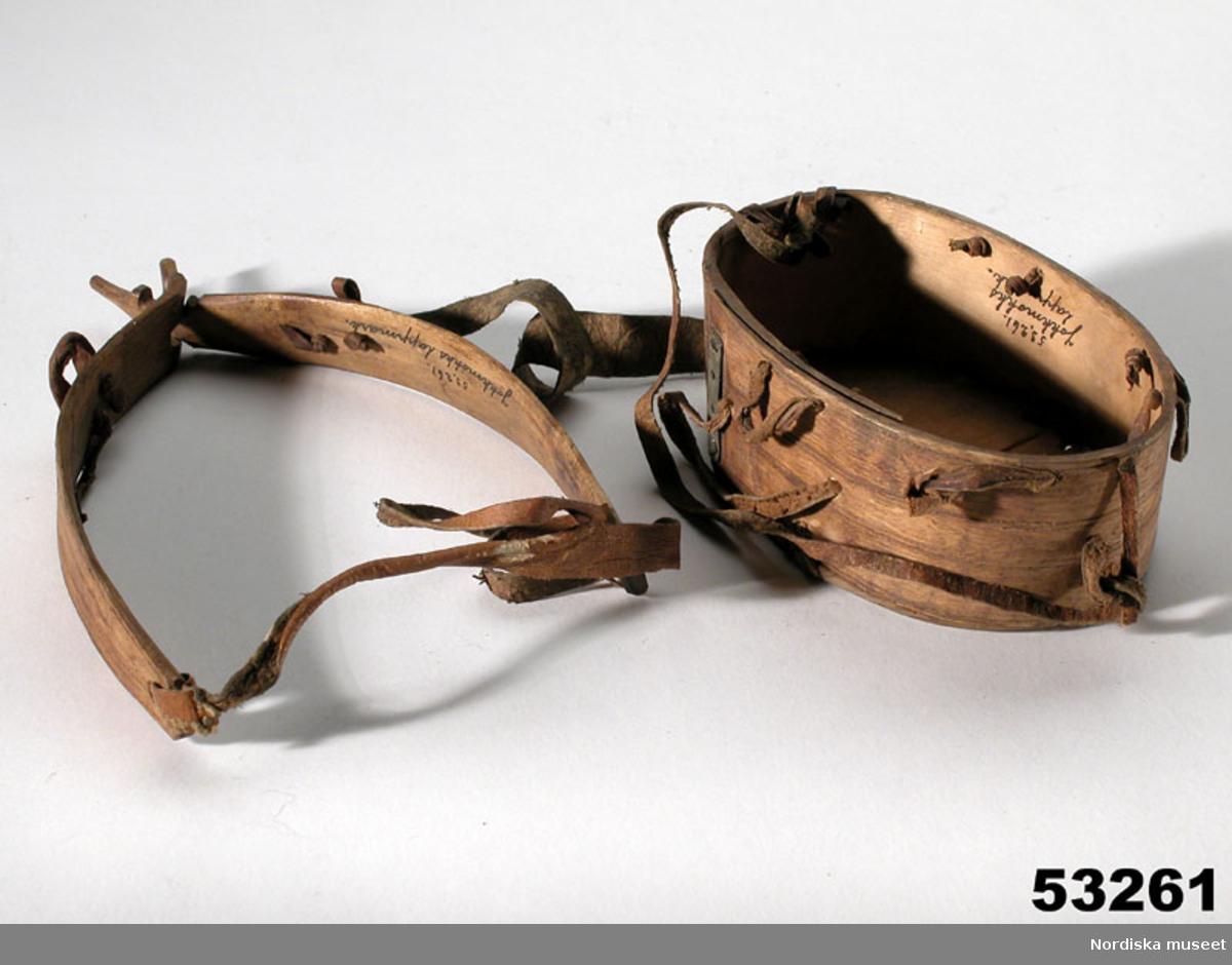 """Huvudliggaren: """"+ Modell till lappkåta fr. Jokkmokks lappmark. Se bilagan 53.261. 26 modellpinnar. Ink. gm Fil. dr. F. Svenonius i Stockholm. Ank. 30/11 1886. Njalla (stolpboden) spräckt. Bil. Svenonius 15."""""""