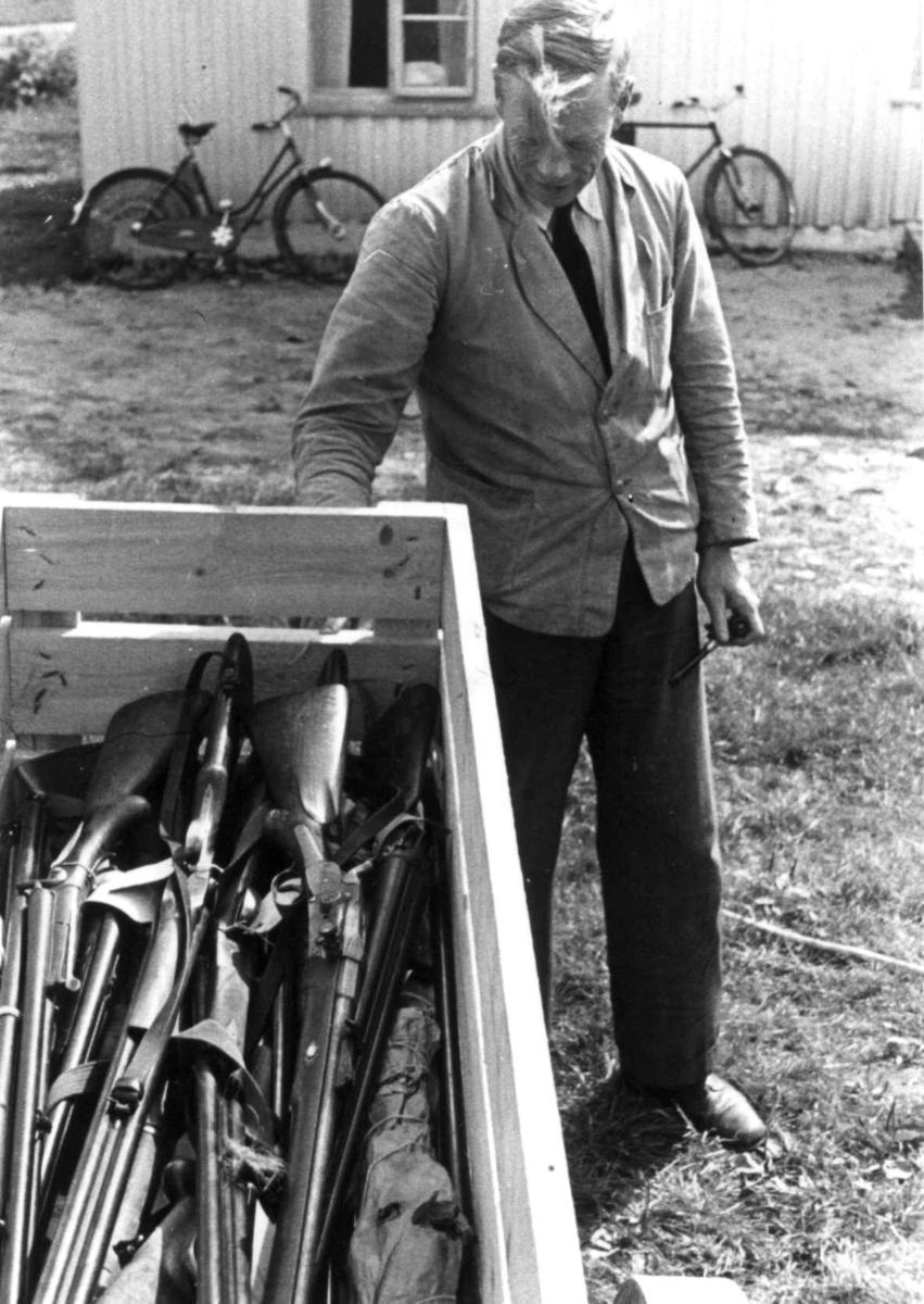 Knut vatnestrøm med en samling våpen i en kasse. To sykler lent mot en husvegg i bakgrunnen. Frostemyr 1941.