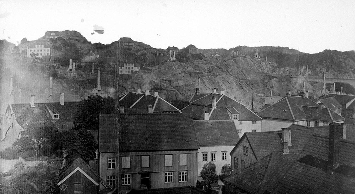 Arendal sentrum med Tyholmen i forgrunnen etter bybrannen 1868. Langbryggen ligger i ruiner i bakgrunnen. Pollen går inn mellom husene og branntomten. Tromøy i bakgrunnen t.h.