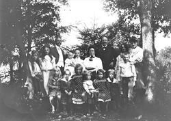 Familiegruppe oppstilt mellom trær.