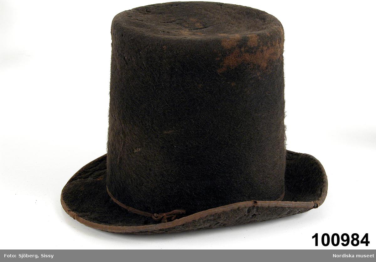 Svart rak cylinderhatt av yllefelb, t, med svängt brätte kantat med brunt bomullsband. Hattband av likadant band .  Svettrem avsvartt läder, en flik svart läder påsytt på undersidan av brättet  där man greppar vid på-och avtagning. foder av vaxad bomullsvävt, Kullens botten helt täckt av rund pappersetikett med tryckt bild av kvinna i 1830-talsdräkt. På bilden hattmakarens etikett : Förfärdigad hos G.Liljedahl i Engelholm. . Jfr med hattar 99651,   9124, 63449. . som har bilder i kullen. /Berit Eldvik 2012-11-02