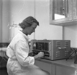 Kvinne foran maskin på sykehus.