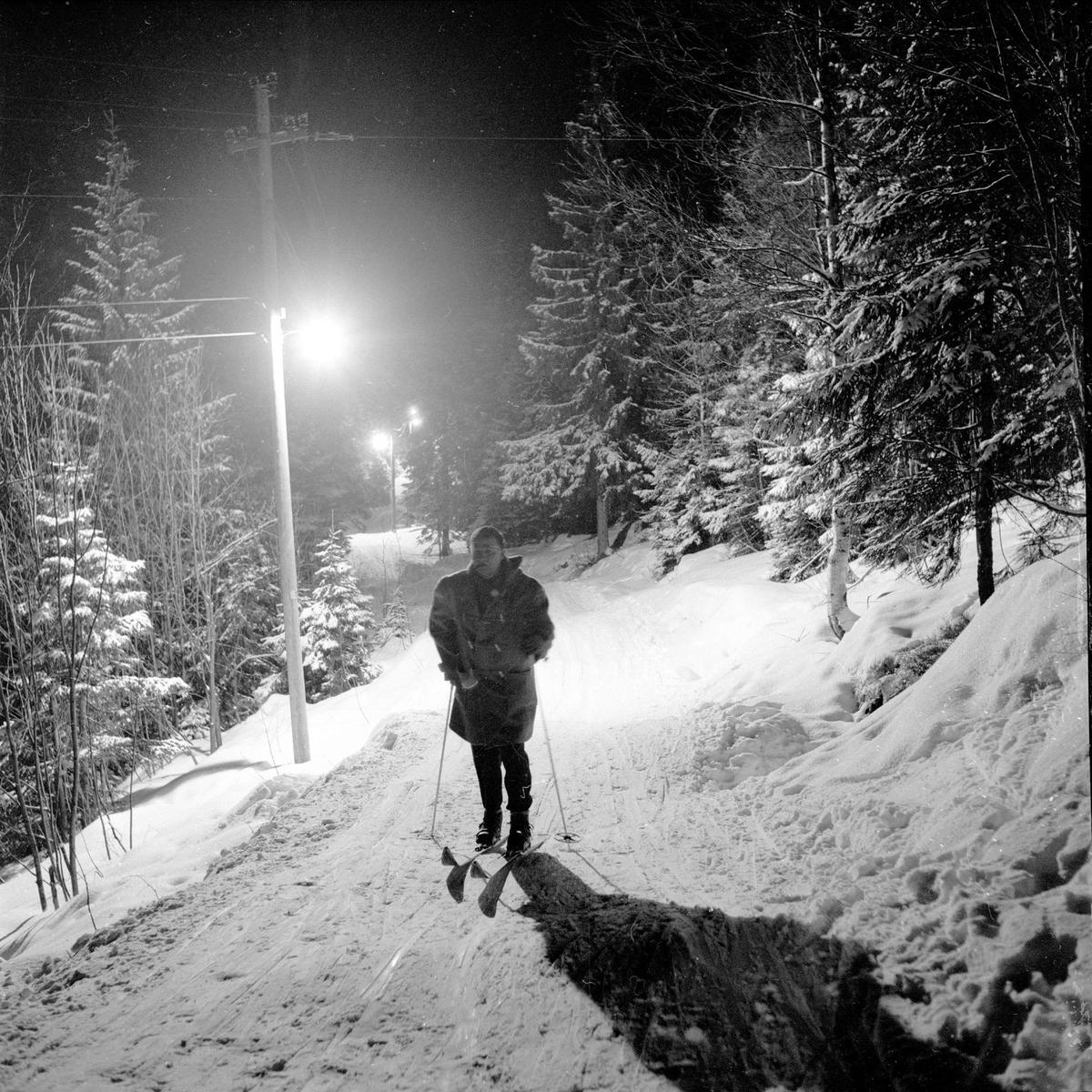 Nordmarka, Oslo, 12.02.1955. Lysløypa. Skiløpere i skogen.