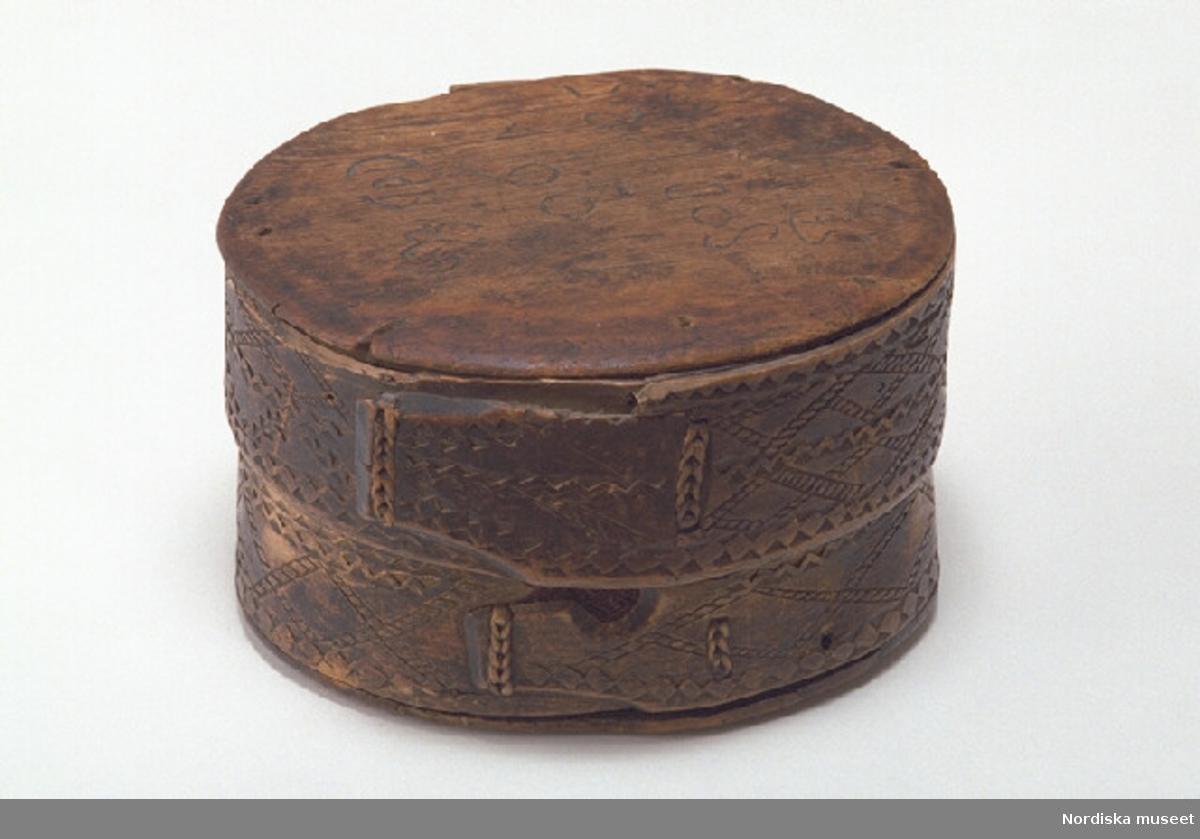 """Inventering Sesam 1997-1998: Diameter 20 (ca), H 10,5 cm Spånask (a) med lock (b), rund. Botten och lock av barrträ, svep av lövträ, med falsar. Svepen är/har varit fästade med dymlingar av trä, på bottensvepet islagna från bottens undersida. Hopfästning av svepen med rottågor, kedjesöm, två rader. Skuren dekor på bottensvepets hopfästning med ett brunt ylletyg mellan svepändarna. Svepen målade i brunt med skuret, geometriskt mönster, bottensvepet med dekor upp till locksvepets nederkant. Inskuret och ristat på lockets ovansida """" 1693 GPD  1706  SOD 1725  SID: FÖD:DEN:9:MAI:1784 """". Bottensvepets insida med ristade linjer. Lockskivan skadad, lös från svepet. Agnetha Blomberg 1997"""