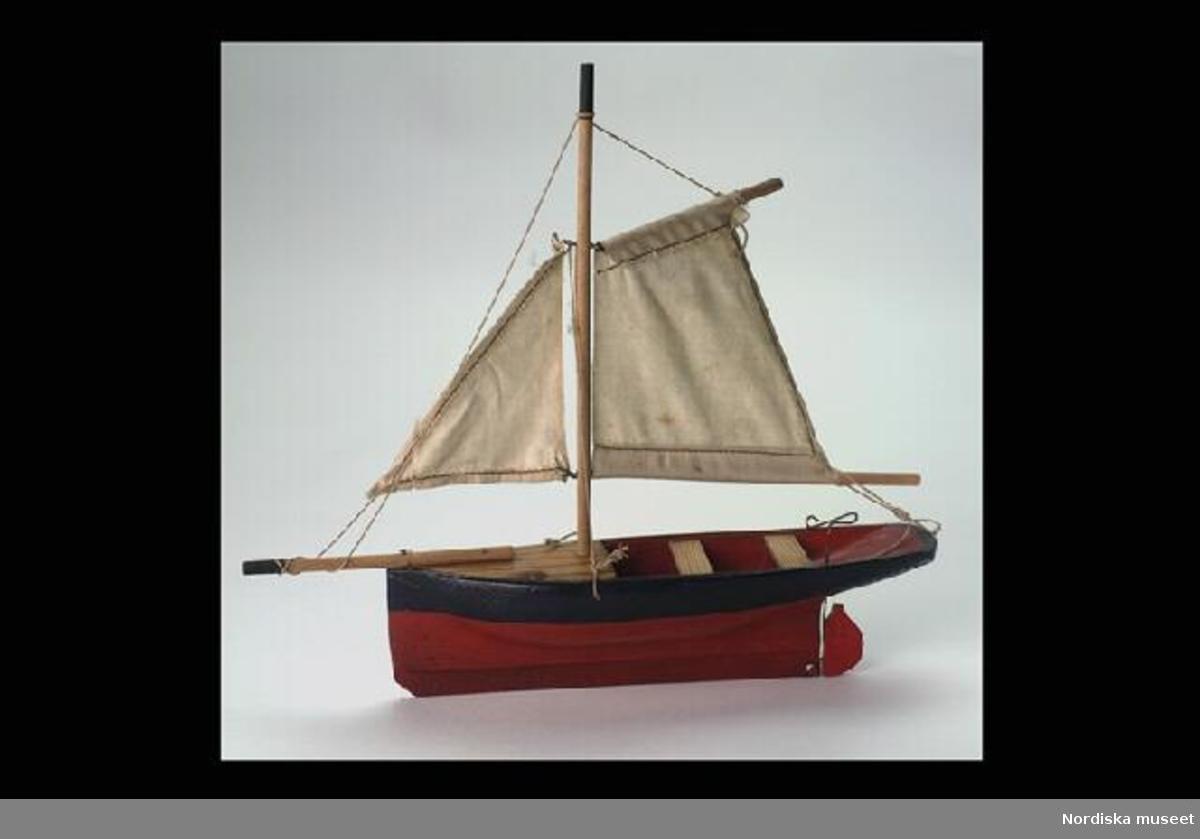 """Huvudliggaren: """"Segelbåt, leksak, av trä, målad röd och svart, med fock och storsegel. Har tillhört Gunnar Alfred Lundgren 1894-1899. G[åva] 20/12 1941 av fröken Iris Lundgren, Stockholm.""""  Inventering Sesam 1996-1999: L 25 cm  B 6 cm H 26,5 cm Segelbåt av trä målad i rött och svart. Rak akter, rak för- och akterstäv. Rorkult av metall och rörligt roder. Har fock och storsegel. Seglet fäst i fören vid bogsprötet, babord och styrbordsidor samt rakt i aktern. Segel av vitt bomullstyg. Står i en träställning. Täckt i fören och aktern av två tofter. AS 1983 Helena Carlsson 1996"""