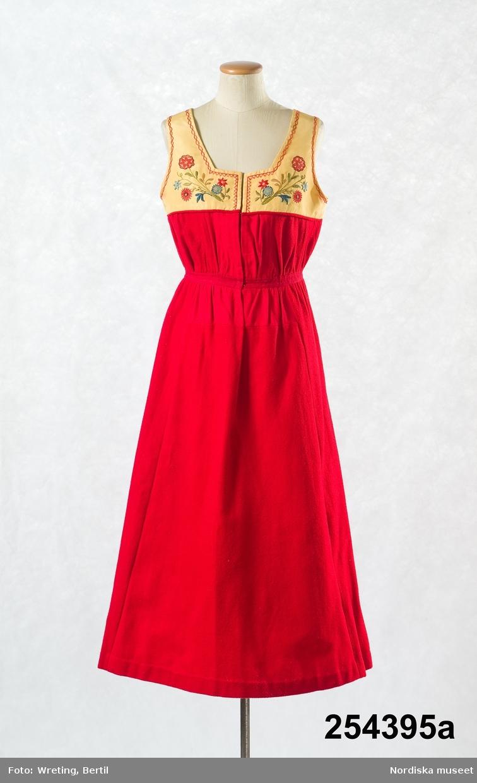"""Rekonstruerad kvinnlig Österåkersdräkt bestående av 7 delar , a.-g.  a. Livkjol b. Överdel c. Rosett d. Förkläde e. Bälte f. Kjolväska g. Huvudbonad  a. Livkjol av rött ylle, avskuren i midjan och rynkad både uppåt  och på kjolen, kort liv av sidenrips med broderier i flät-stjälk- och plattsöm med silke i flera färgerLivet fodrat med gulvit bomullslärft. b. Överdel, blus av vit bomullslärft, skuren i ett stycke med blusande ärmar och öppen fram. Ärmarna har breda uppvikta handlinningar med tryckknappar. Garnerad med maskingjord brodyr. c. Grön sammetsrosett att ha i halsen. d. Förkläde av tunt grönt ylle i satinbindning ( för att likan rask) broderad bård på¨förklädet samt på midjelinningen i med silke i flera färger som på livet samt bandgarnering.Skoning av svart ylletyg märkt H.J. maj 1892 i stjälksöm med silke. d. Bälte av rött saffianskinn med silkebroderier i ljusblått, gult och vitt, försedd med spänntamp och sölja dold under bältesfliken. f. Kjolväska av blått ylletyg med applikation i form av solros och gröna blad av kläde, något silkebroderi. Bakstycke av rött ylle samt band av röd yllekypert. g. Huvudbonad  s.k """"huckel"""" bestående av röda valkar, spetsluva och tyllhuckle.  Sydd till givaren 1892. Använd på Skansens vårfester under Artur Hazelius tid. Hilma J. var född 1875. Österåkersdräkten hörde till de folkdräkter som tidigast rekonstruerades och började användas av borgerliga damer under 1890-talet jämte Delsbodräkt, Rättviksdräkt och Blekingedräkt. Inte minst viktig för spridningen var att kronprinsessan Victoria bar denna dräkt under sina vistelser på Tullgarns slott och en i stort sett identisk dräkt kom också att kallas Tullgarnsdräkt.  Berit Eldvik juni 2005"""