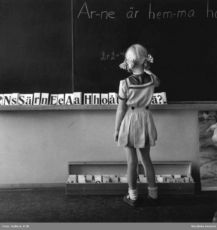 Skola och undervisning. Flicka med margaretaflätor skriver på svarta tavlan i småländsk folkskola.
