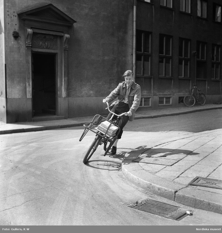 Cykelbud i Stockholm. Pojke cyklar på en stadsgata, vänstertrafik. På pakethållaren ligger paket.