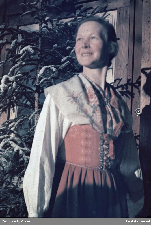 Dalarna. På Långbergsgården i Tällberg på vintern med kvinna i folkdräkt och bakom henne en gran.